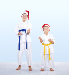 Younger and older brother in caps of Santa Claus standing in the rack of karate
