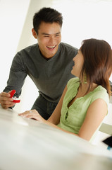 Man presenting woman with ring in box