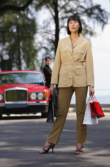 Woman carrying shopping bags, looking at camera, man in the background, leaning on car
