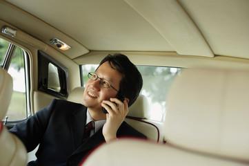 Businessman sitting inside car, using mobile phone