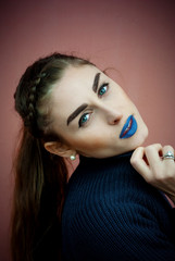 Teenager with braid and blue makeup