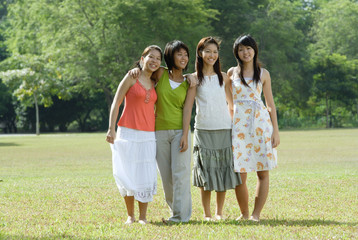 Young women standing side by side in park