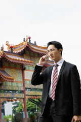 Businessman standing in front of Chinese temple, using mobile phone