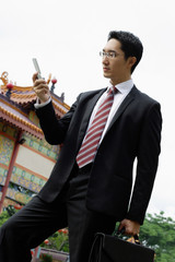 Businessman standing in front of Chinese temple, text messaging