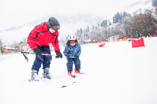 Happy little boy learning skiing with his father in Kitzbühel, Tyrolian Alps, Austria