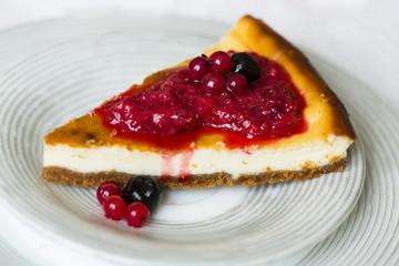 Чизкейк/творожный пирог с красными ягодами/красной смородиной на белой тарелке, палочки корицы, связанные красной нитью и горящая свеча и конфеты в красный обертках