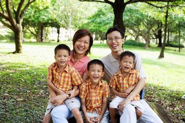Family with three boys in park, smiling at camera