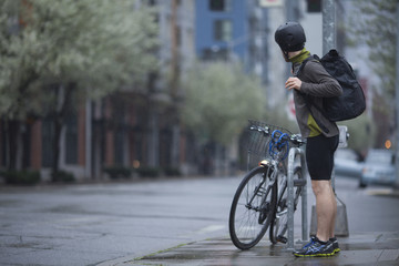 An adult man, stopped on a Seattle, Washington street corner, preparing for a rainy morning bike commute.