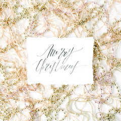 calligraphy words merry christmas and christmas tinsel decoration. flat lay, top view