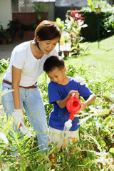 Mother and son watering plants in garden