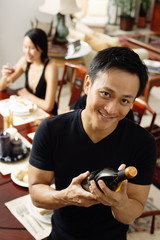 Man looking at camera, holding wine bottle