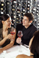Young adults in restaurant, holding wine glasses