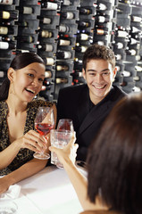 Young adults in restaurant, holding wine glasses, toasting