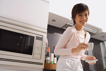 Young woman in kitchen, holding cup and saucer, smiling