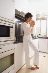 Young woman standing in kitchen, drinking coffee