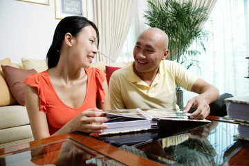 Couple at home in living room, looking at each other, photo album in front of them