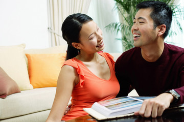 Couple at home, smiling at each other, photo album in front of them