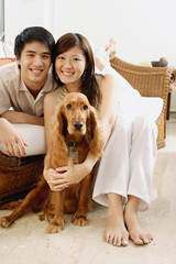 Couple in living room, with Cocker Spaniel dog