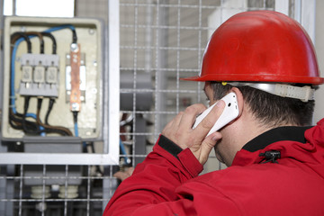 Engineer in red control high voltage fuse in power plant