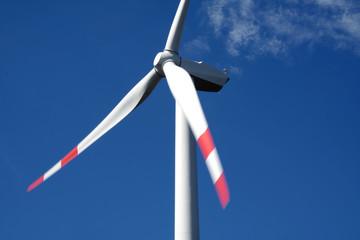 Pala eolica bianca con pale con estremità rosse nel cielo azzurro