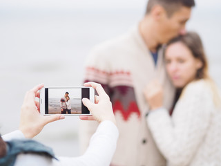 Photographer takes a shot of young couple with a phone