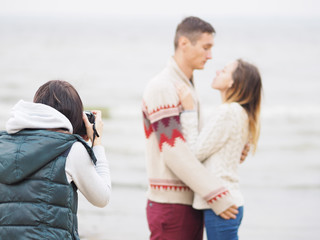 Photographer takes a shot of young couple with a dslr camera