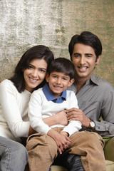 family of three smiling at camera (vertical)