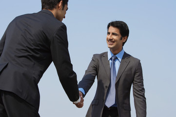 two businessmen shake hands (horizontal)