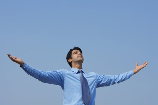 businessman with arms outstretched, eyes closed