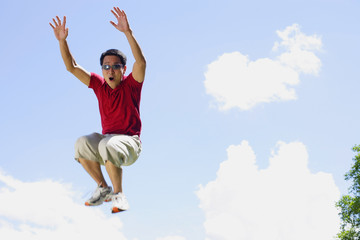 Man jumping in mid air, arms outstretched, mouth open
