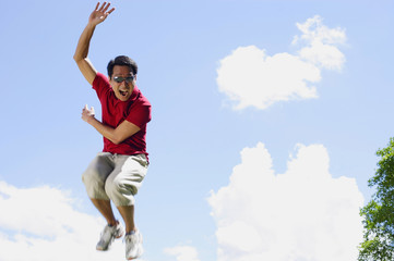 Man jumping in mid air, hand raised, mouth open