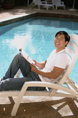 Young man relaxing in deck chair by the pool