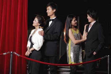 Young people standing behind red rope at night
