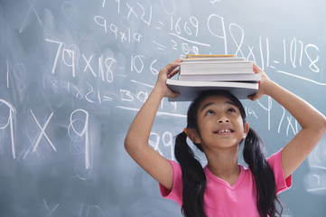 girl with books stacked on head, looking up (horizontal)