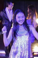 Young woman dancing at night with people in background