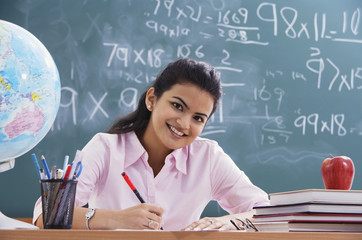 teacher at desk, smiling at camera (horizontal)