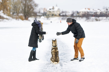 Woman and man play with dog in snow
