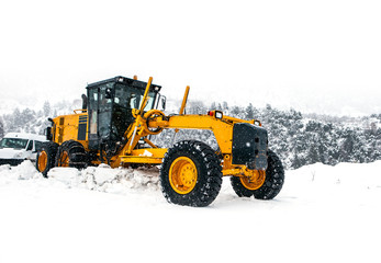 The bulldozer cleans snow on road