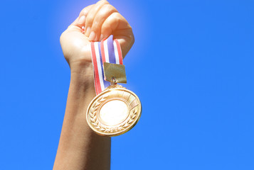 hand raised and holding gold medal against blue sky. award conce