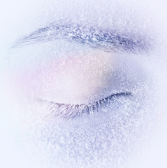 Closed eye with frost or snow on eyelashes macro close-up in winter on a light blue background. Gentle romantic dreamy artistic image.