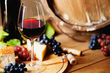 Wine glass, cheese, grapes and barrel