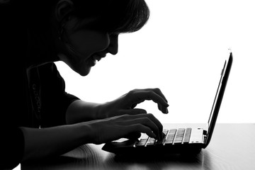 silhouette of a hacker typing on the keyboard of laptop
