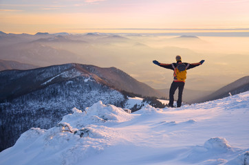 man with open arms over wonderful mountains landscape in mist during calm winter evening