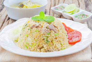 Fried rice with chili sauce and soup on wooden table