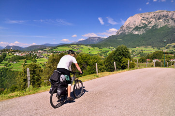 Man on bike travel on road over the valley with Italian houses. Summer sport vacation scenery.