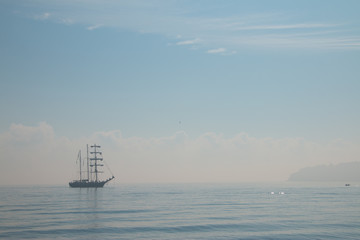 Tall ship sailing in the sea in foggy misty day.