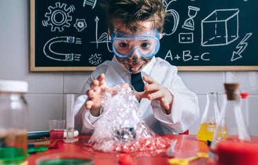 Portrait of happy little boy scientist with glasses and dirty face opening his arms behind of glass with soap foam