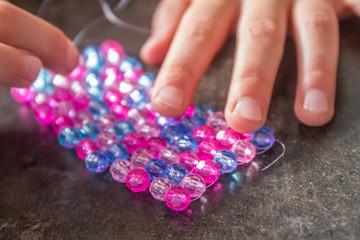 young child girl making bead bracelet, indoor portrait