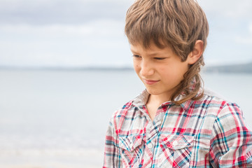 outdoor portrait of young boy on natural sea background