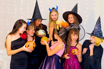 Happy group of teenagers in Halloween costumes posing on camera